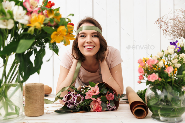 Cheerful florist woman with flowers in workshop - Stock Photo - Images
