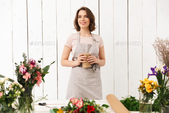 Pretty smiling florist woman with different flowers - Stock Photo - Images