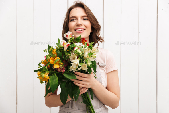 Cheerful florist woman standing with flowers - Stock Photo - Images