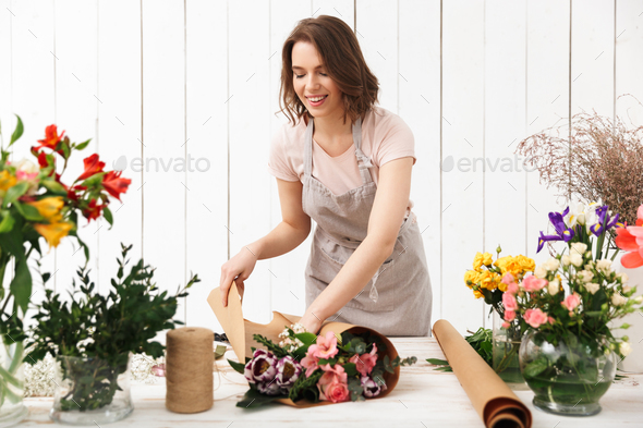 Happy florist woman working with flowers in workshop. - Stock Photo - Images