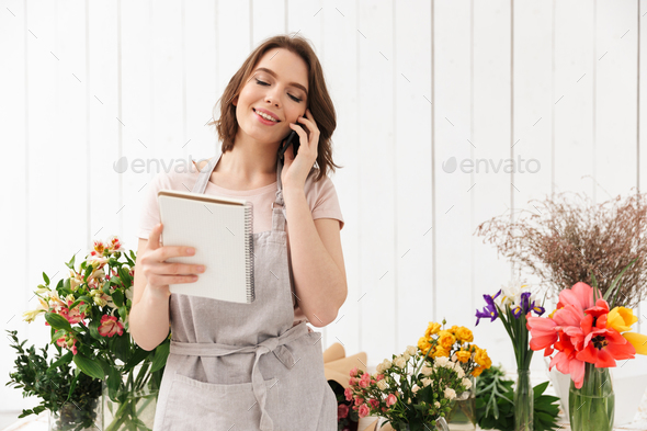 Young florist woman standing near table with different flowers i - Stock Photo - Images