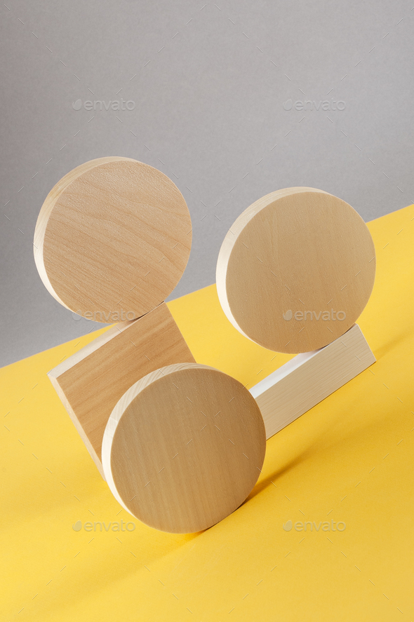 Abstraction from round wooden geometric figures on a gray-yellow - Stock Photo - Images