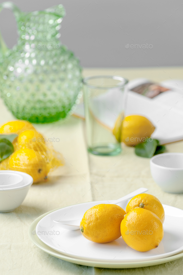 Ripe lemons on a plate on a table covered with a light green tab - Stock Photo - Images