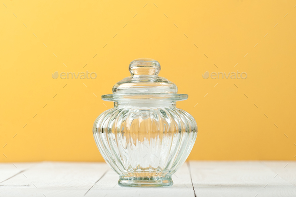 Glass jar with a lid on a white table near the yellow wall. - Stock Photo - Images