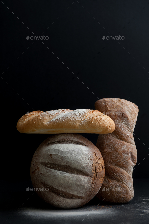 Freshly baked different breads on a black background. - Stock Photo - Images