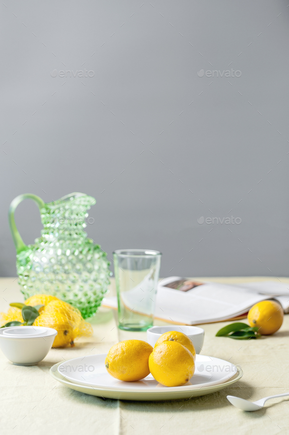 Ripe lemons on a plate, a jug, a glass and a book on the table. - Stock Photo - Images