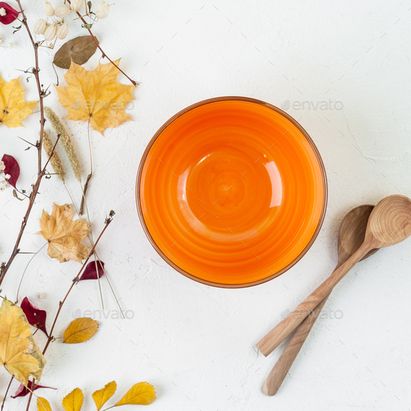 Bright orange empty bowl, wooden spoon and autumn leaves on a wh - Stock Photo - Images