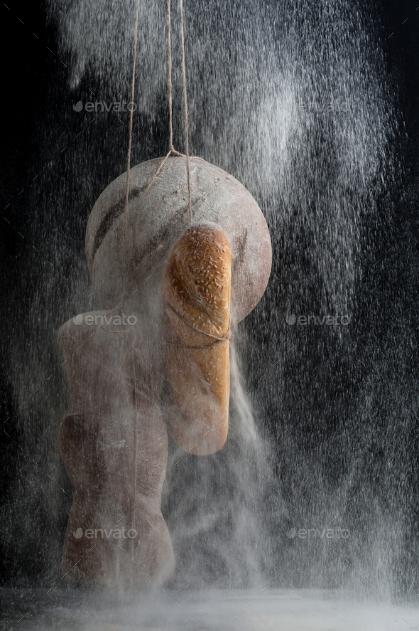 Three kinds of fresh bread in a floury fog on a black background - Stock Photo - Images
