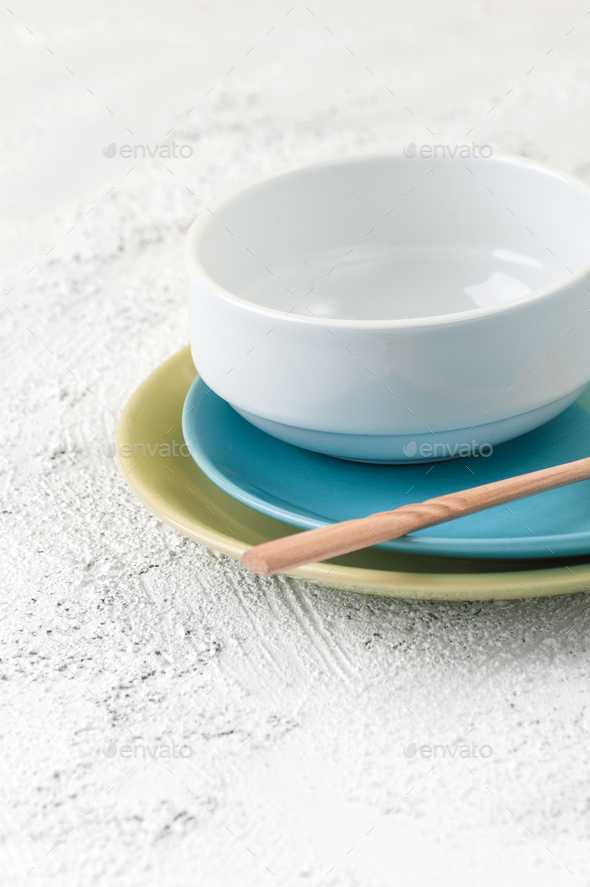 Plates, bowl and wooden spoon on a light gray textural backgroun - Stock Photo - Images
