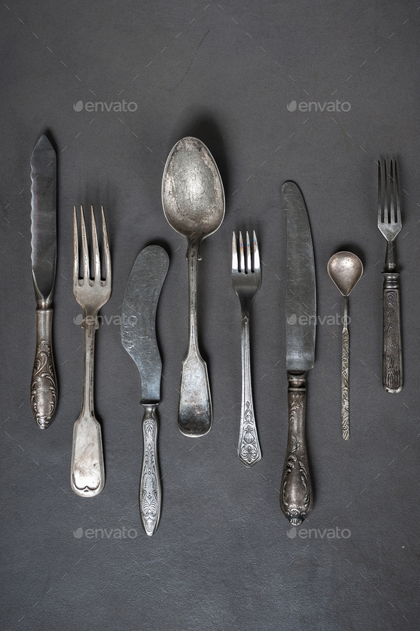 Vintage cutlery on a gray stone table. - Stock Photo - Images