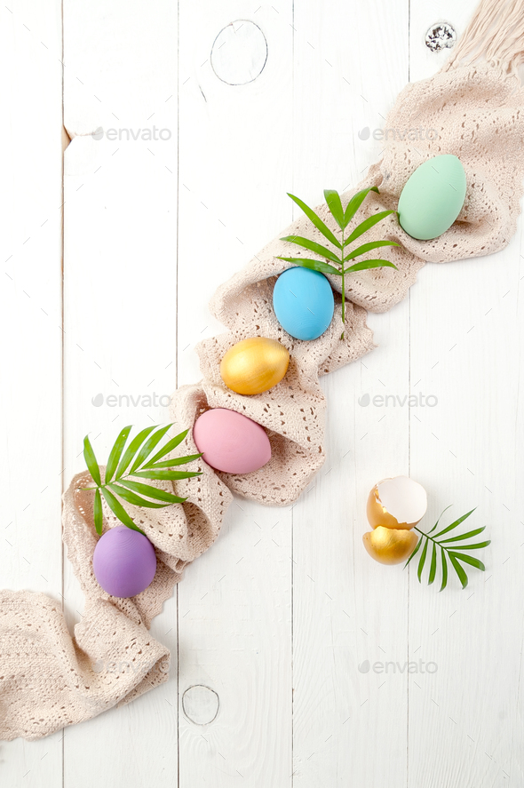 Multicolored easter eggs of pastel and gold color on a white woo - Stock Photo - Images