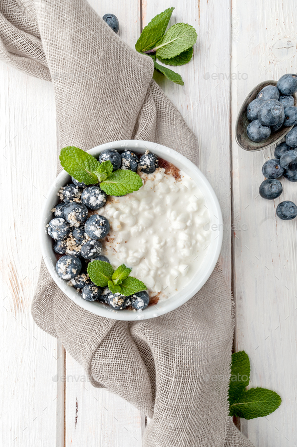 Cottage cheese with fresh blueberries and mint leaves on a white - Stock Photo - Images