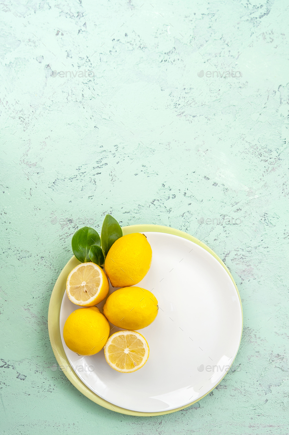 Ripe lemons on a plate on a mint-colored table. Flatt-barking. - Stock Photo - Images