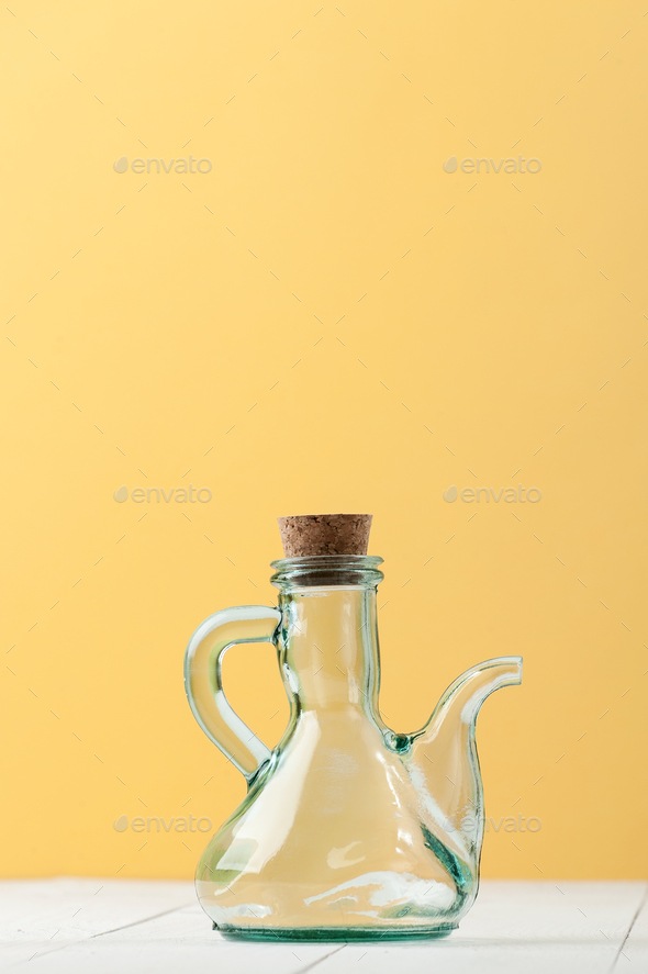 A glass jug with a natural cork on a white-and-yellow background - Stock Photo - Images