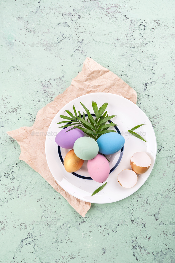 Colored easter eggs and green leaves on a round white plate on a - Stock Photo - Images