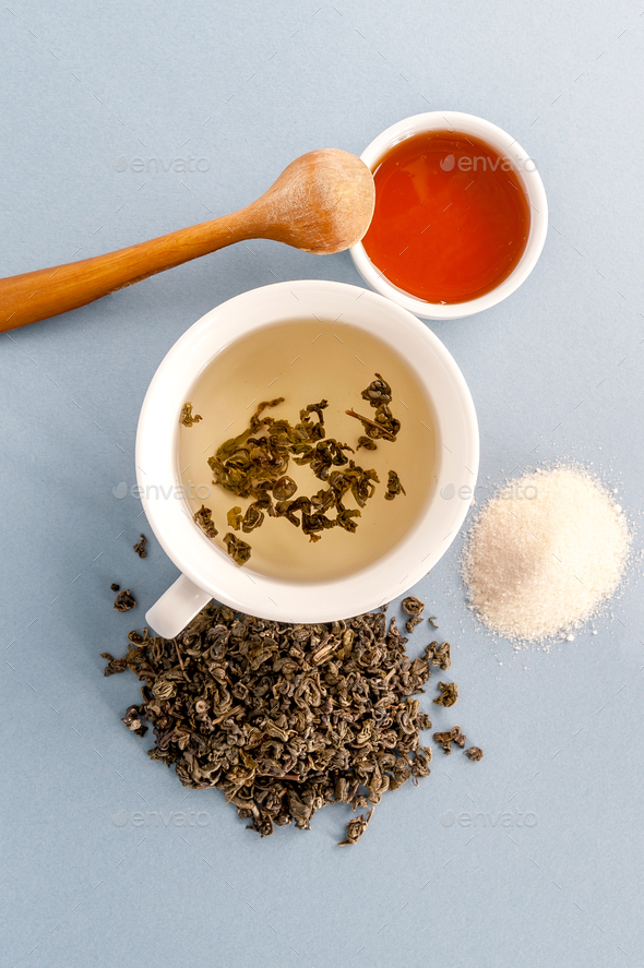 Green tea in a cup and honey. Flat-lay on a light blue backgroun - Stock Photo - Images
