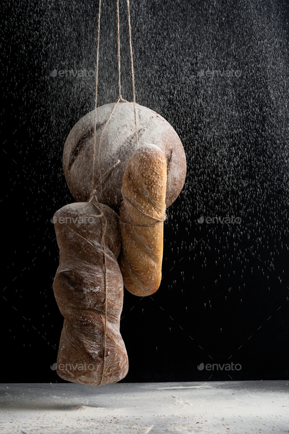 Three kinds of fresh bread in a fog of flour on a black backgrou - Stock Photo - Images