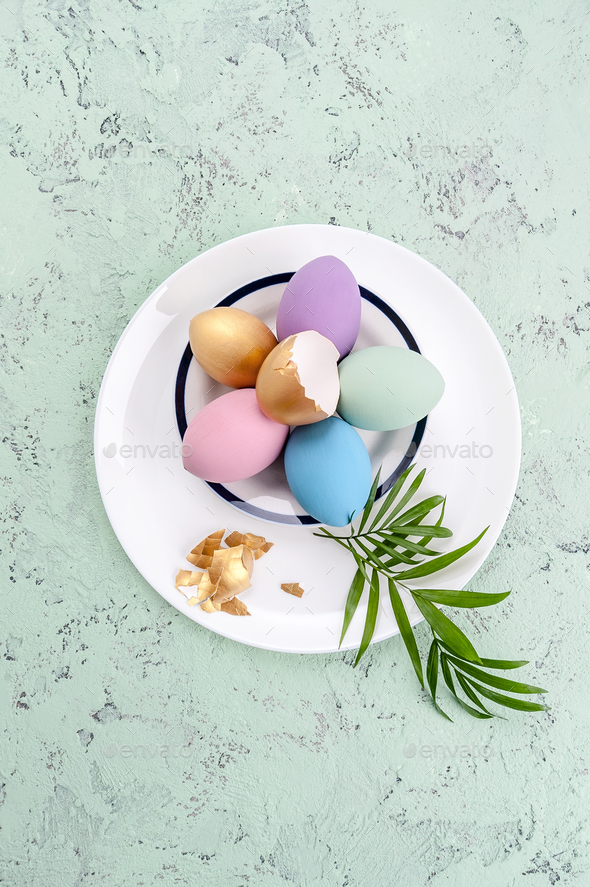 Colored easter eggs and green leaves on a round white plate. - Stock Photo - Images