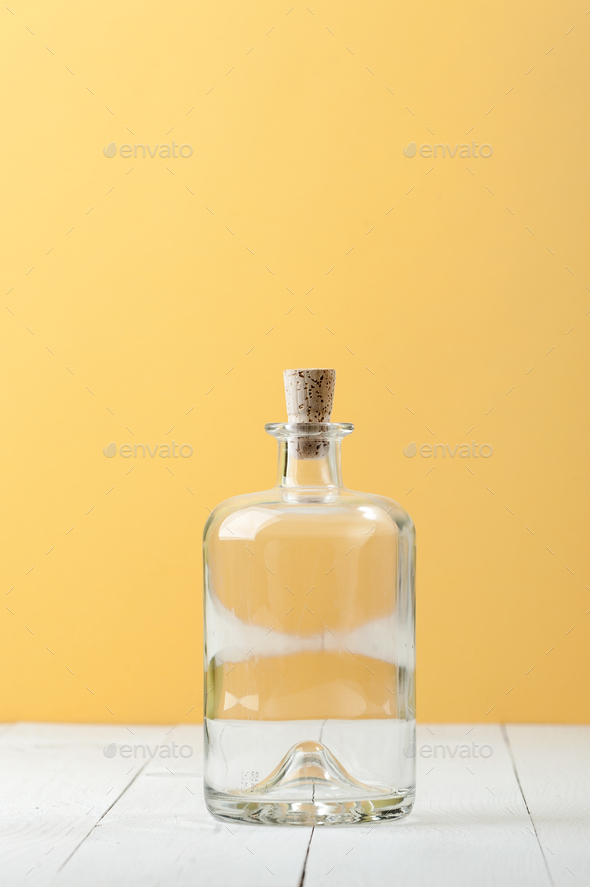 Empty glass bottle for rum on a light white-yellow background. - Stock Photo - Images
