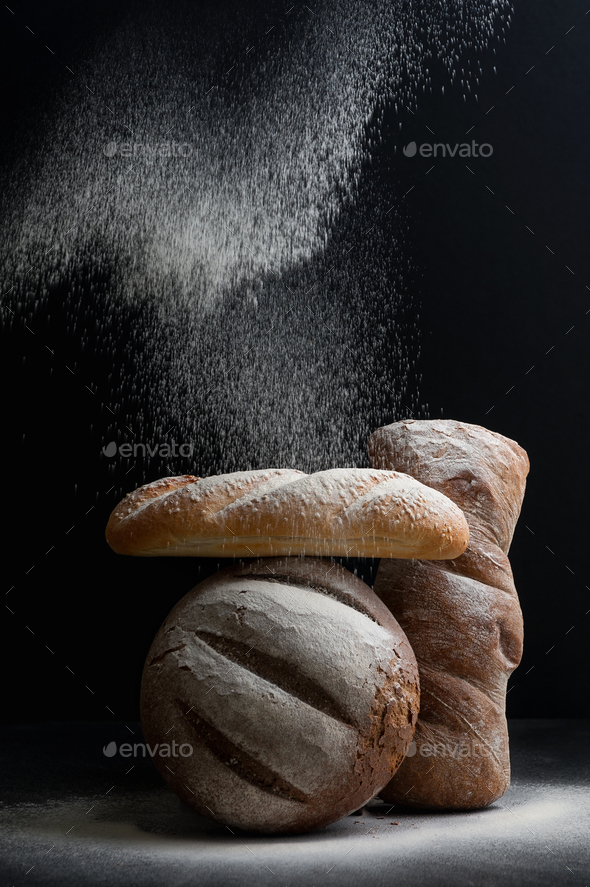 Freshly baked different bread on a black background, on which fl - Stock Photo - Images