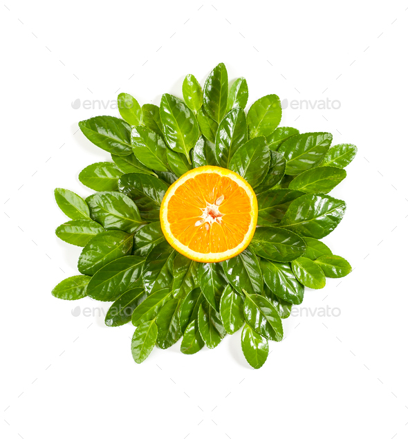 Half of a ripe orange on a background of leaves of a Beresket pl - Stock Photo - Images
