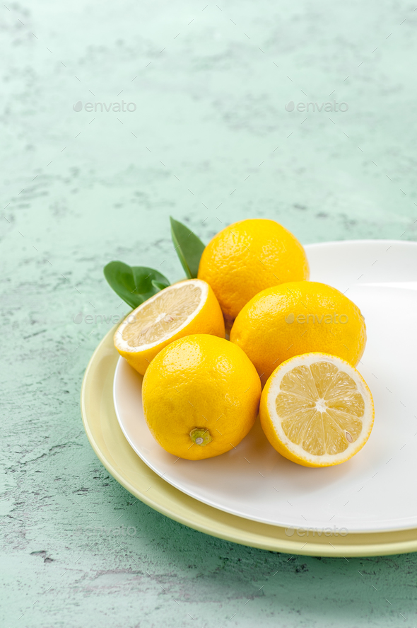 Ripe lemons on a plate on a mint-colored table. - Stock Photo - Images