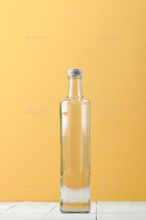 Straight long glass bottle on a light white-yellow background. - Stock Photo - Images