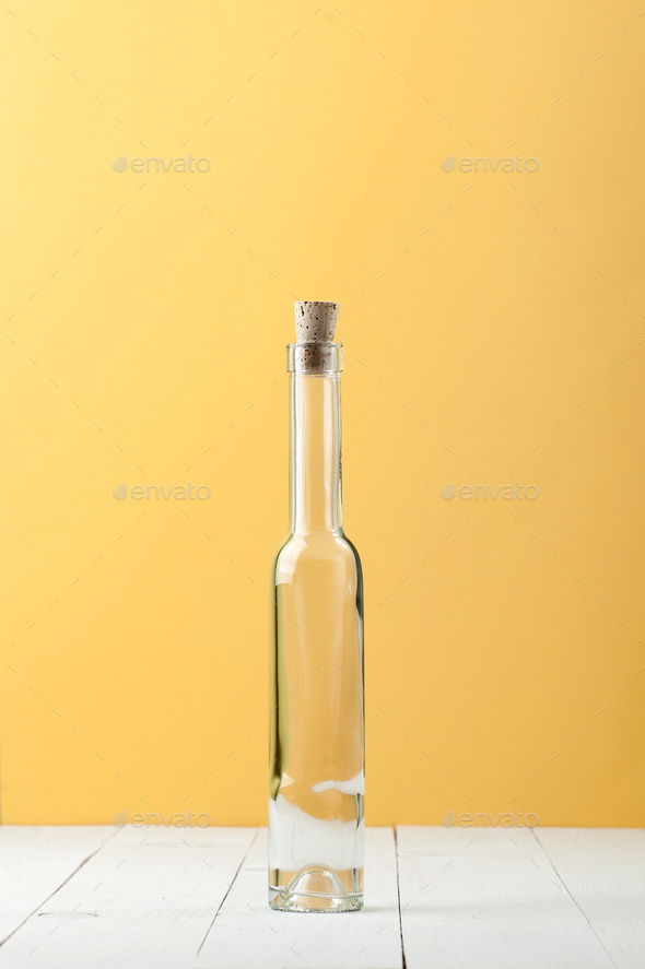 A narrow long glass bottle on a light white and yellow backgroun - Stock Photo - Images