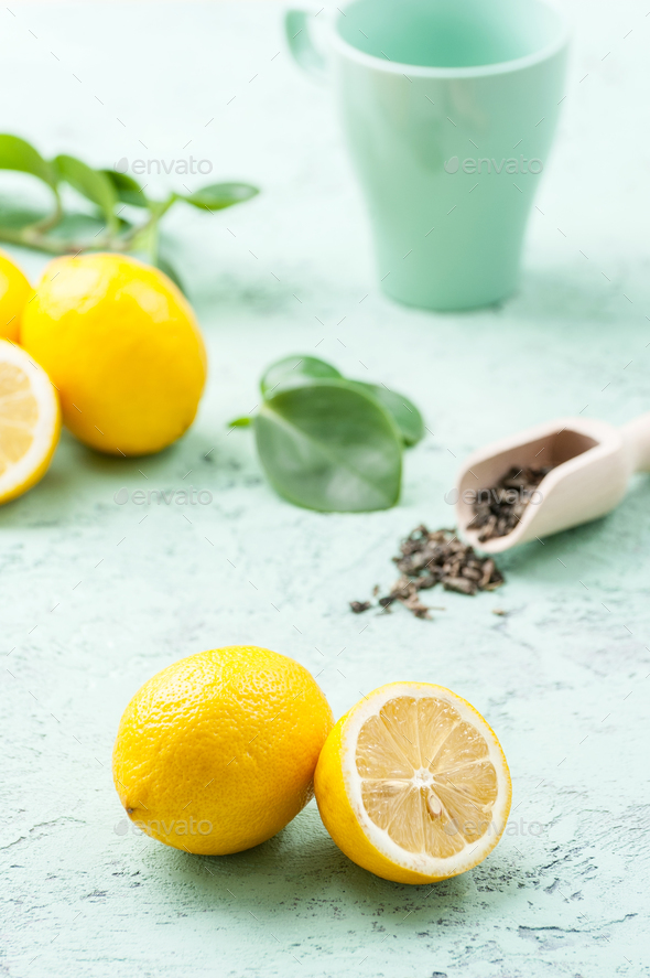 Ripe lemons, tea leaves and a cup on a mint-blue background. - Stock Photo - Images