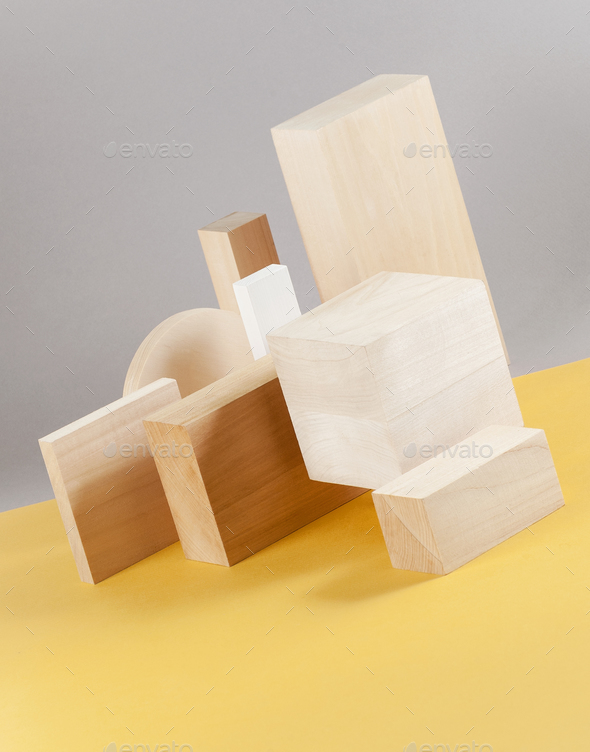 Installation of wooden geometric shapes on a light gray-yellow b - Stock Photo - Images