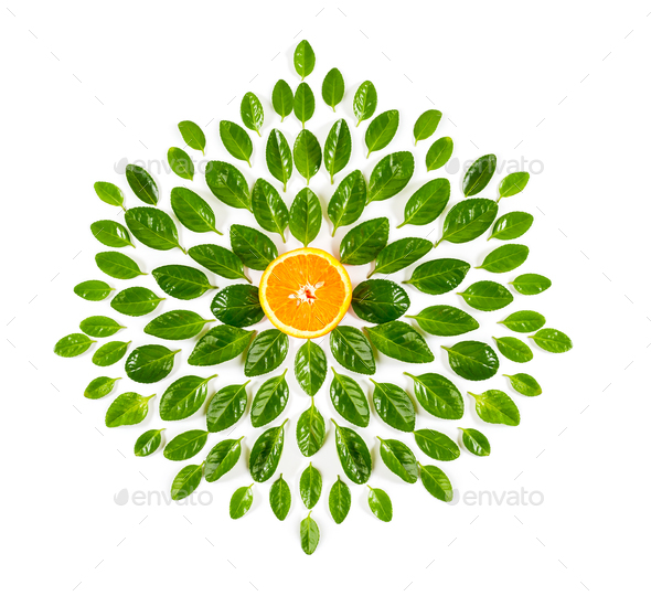 Half an orange and green leaves in the shape of a flower on a wh - Stock Photo - Images