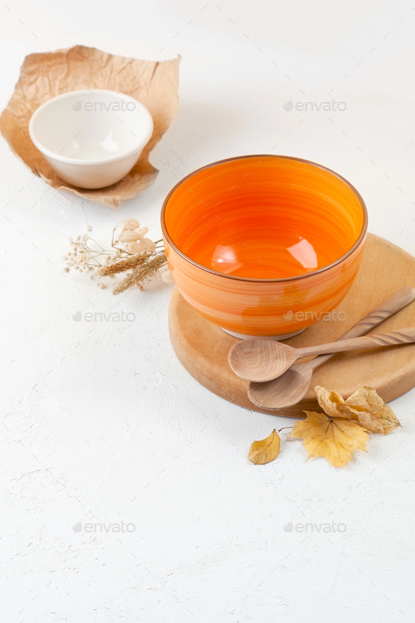 Orange bowl on a stand and wooden spoons on a bright orange back - Stock Photo - Images