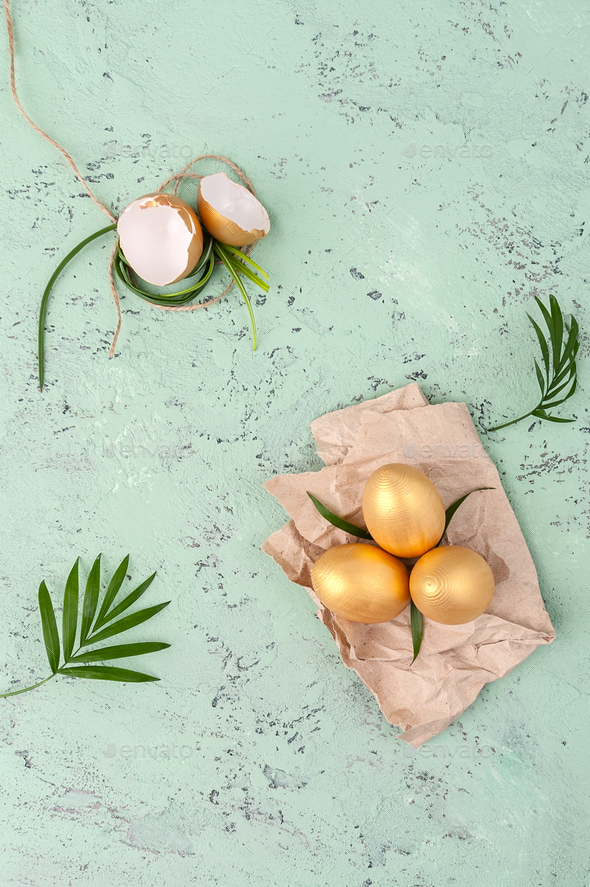 Golden easter eggs and green leaves on a stelo-blue background. - Stock Photo - Images