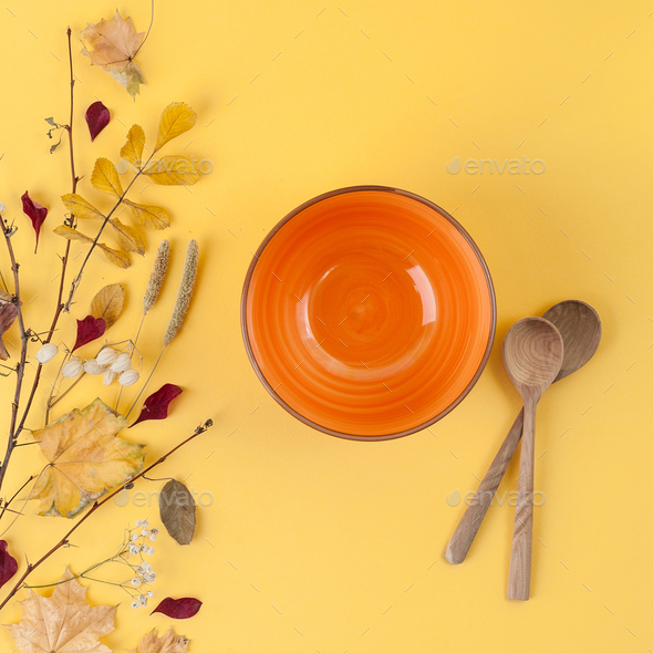 Bright orange empty bowl, wooden spoon and autumn leaves on a ye - Stock Photo - Images