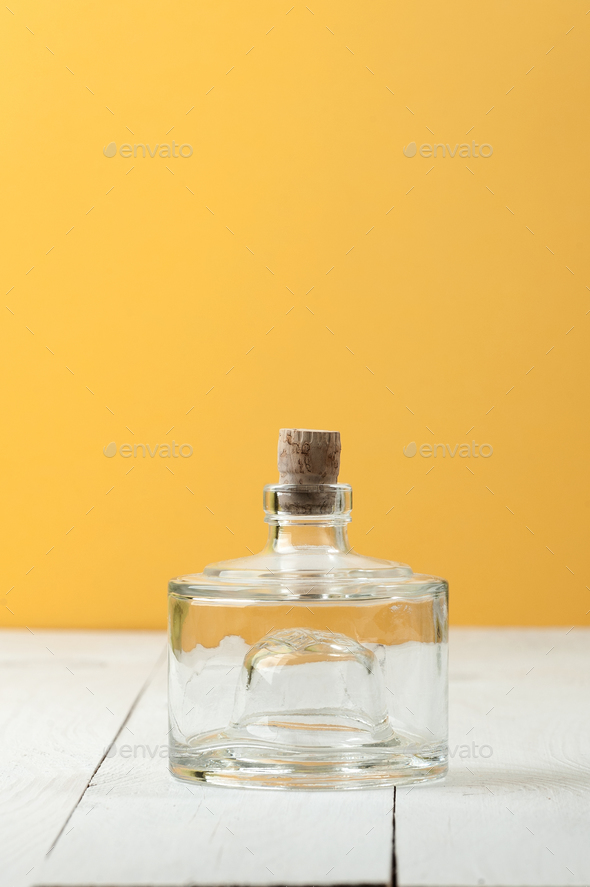 A glass low bottle with a natural cork on a white-and-yellow bac - Stock Photo - Images