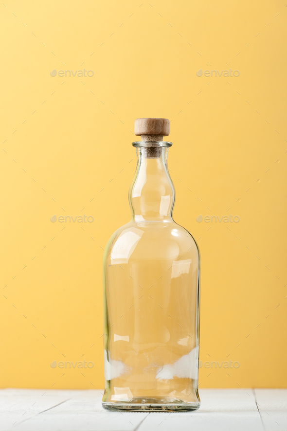 An empty relief glass bottle on a light white-yellow background. - Stock Photo - Images
