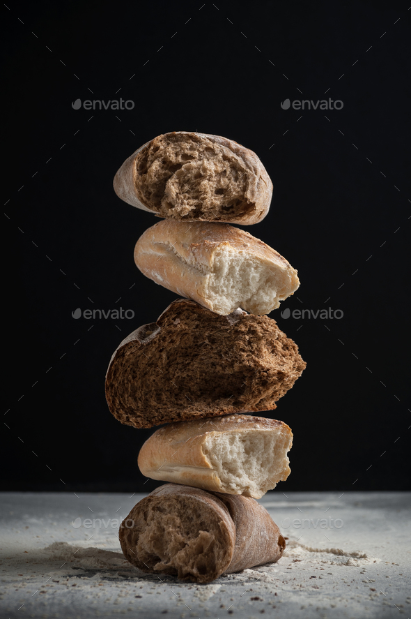 Pieces of different cracked fresh bread on a black background. - Stock Photo - Images