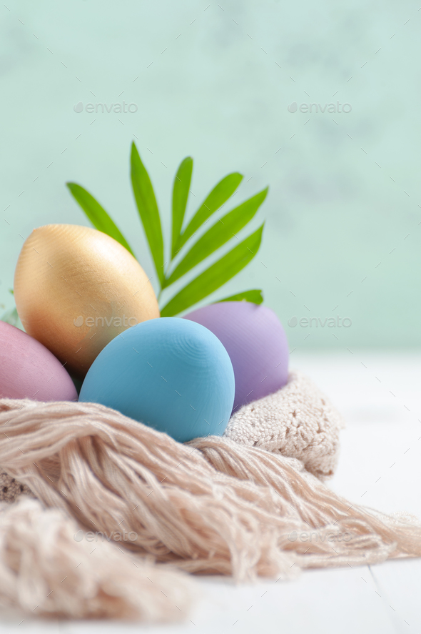Easter eggs pastel and golden colors on a white wooden table. - Stock Photo - Images