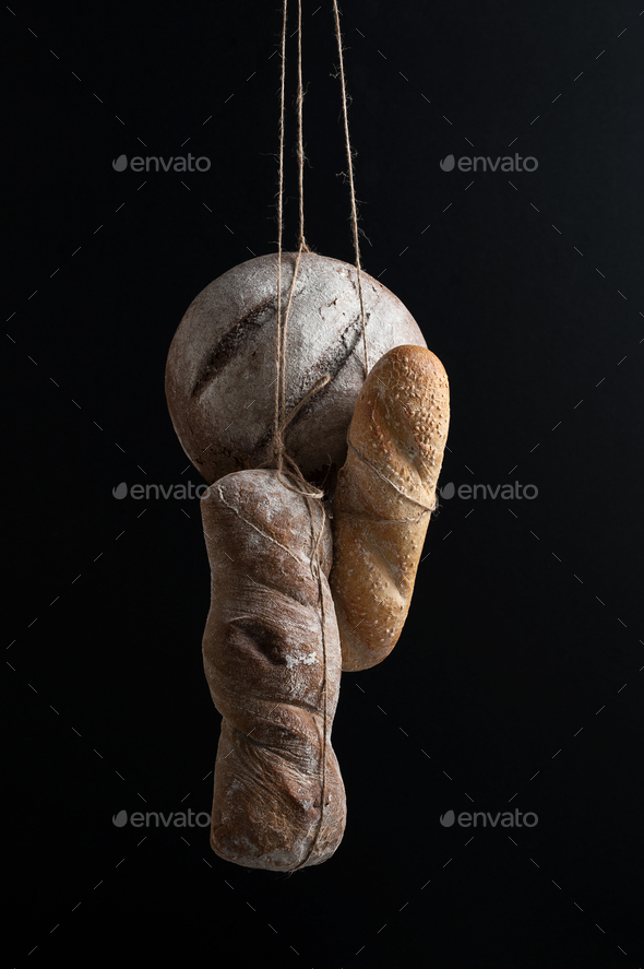 Three kinds of bread hang on a scaffolding on a black background - Stock Photo - Images