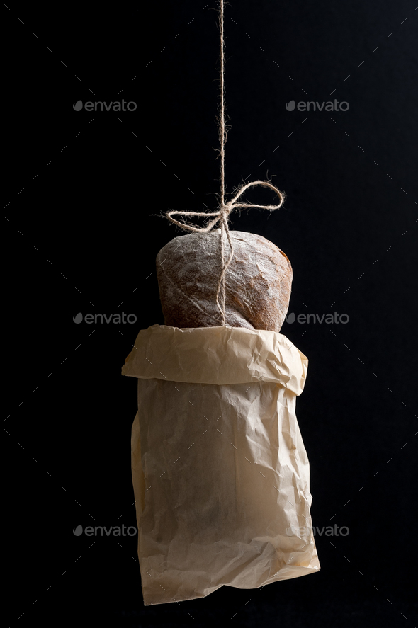 Fresh bread in a paper bag on a black background. - Stock Photo - Images