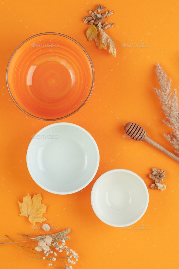 Three empty bowls of different sizes on a bright orange backgrou - Stock Photo - Images