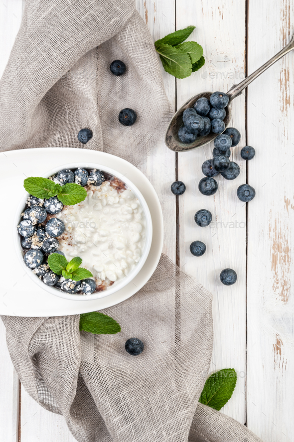 Cottage cheese with fresh blueberries and green mint leaves on a - Stock Photo - Images
