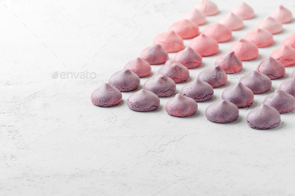 Multicolored meringues in purple-pink colors on a white table. - Stock Photo - Images