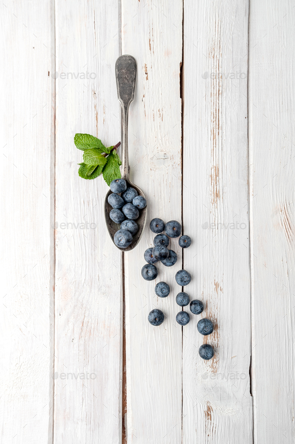 Blueberries in a vintage spoon on a white wooden table. - Stock Photo - Images