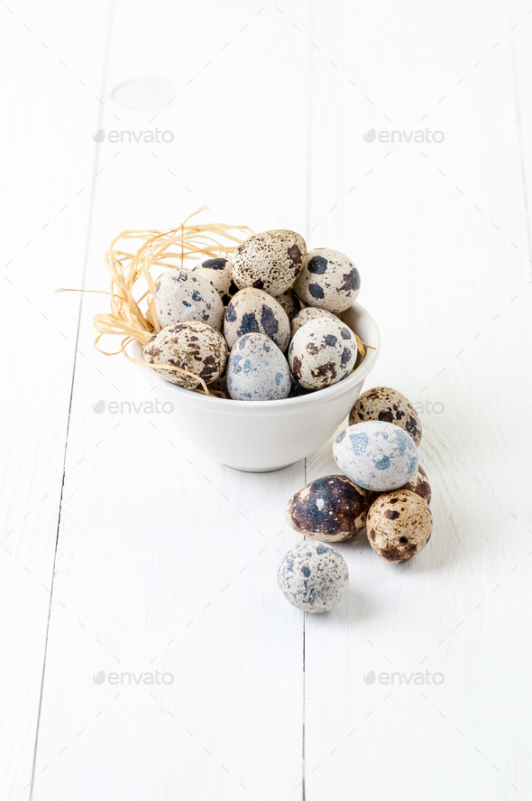Fresh quail eggs in a white bowl on a white wooden table. - Stock Photo - Images