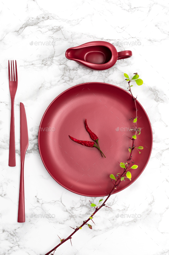 Red ceramic plate, cutlery and sauceboat on a marble table. - Stock Photo - Images