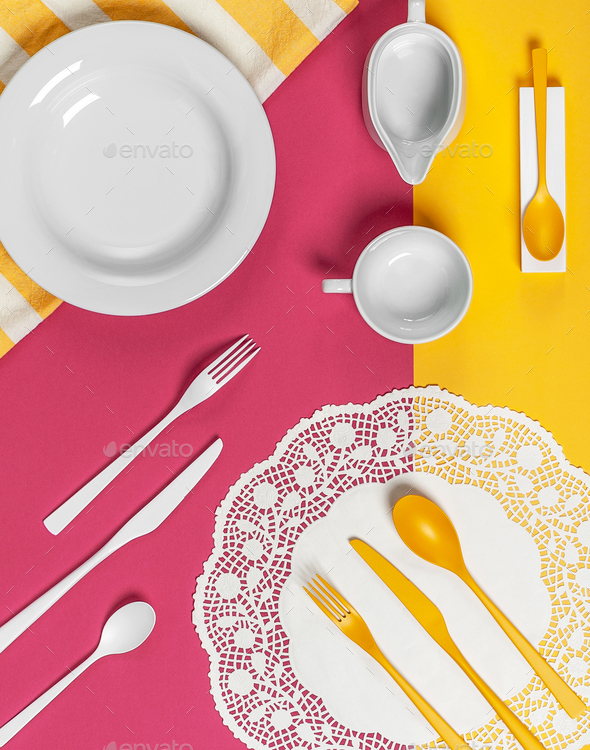 White dishes and yellow cutlery on a yellow-pink background. - Stock Photo - Images