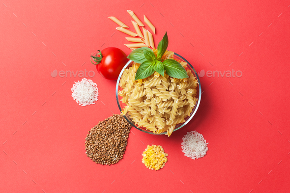 Pasta, rice, buckwheat and lentils, tomato and basil on a red ba - Stock Photo - Images