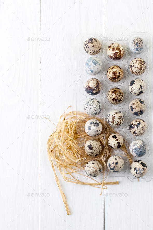 Quail eggs in a package on a white wooden background. - Stock Photo - Images