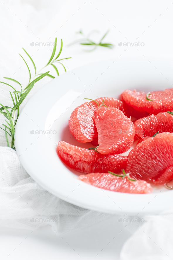 Peeled slices of ripe grapefruit and a branch of fresh rosemary - Stock Photo - Images